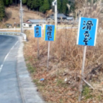 岐阜県恵那市にあった、 「根性で」「曲れ!」という看板。