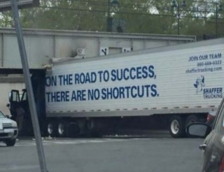 「成功への道程にショートカットは無い」と大書きされたトレーラーが近道しようとして大変なことに。